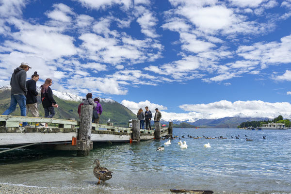 Tourists on a small jetty on Lake Wanaka, a popular tourist destination at the heart of the Otago Lakes. Wanaka township is the gateway to Mount Aspiring National Park. Otago, New Zealand