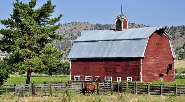 Traditional red-painted timber barn in the Eagle Cap Wilderness, Wallowa Mountains, northeastern Oregon, USA
