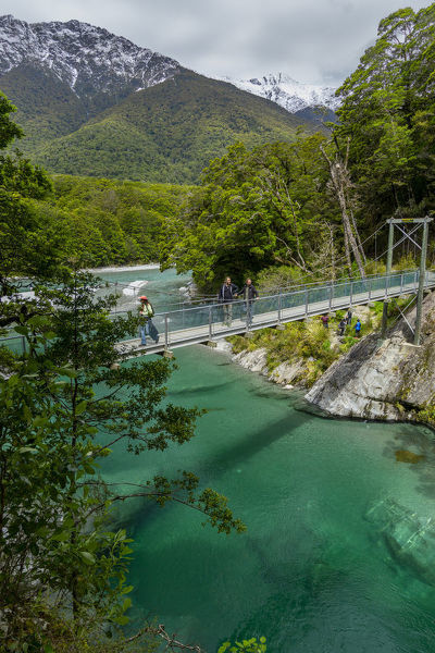 Tramper on the swing bridge over the Makarora River. The Blue Pools Track takes trampers along the river for 1.5 km in spectacular scenery. Mount Aspiring National Park, Otago, South Island, New Zealand