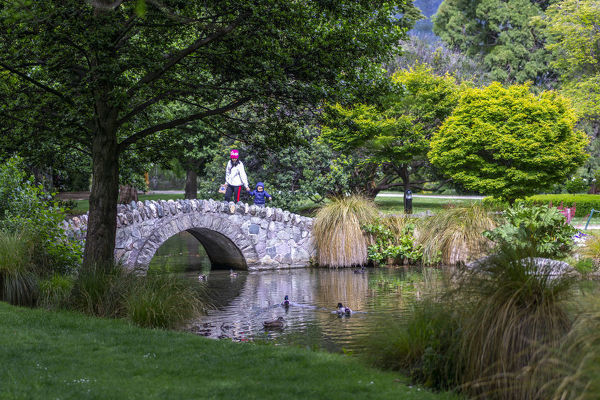 Visitor strollng over a stone bridge of the lake in Queenstown Gardens, a botanical garden created in 1867. Queenstown, Central Otago, South Island, New Zealand