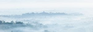 Borobudur glimpsed through the early morning mist lying in the Kedu Valley,
