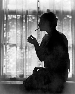 ca 1926: silhouette of young woman lighting a cigarette