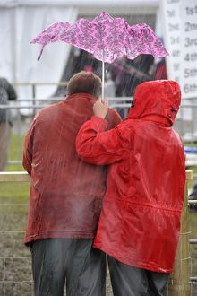 Couple in wet-weather gear sheltering under a small and inefficient umbrella during