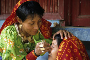 Kuna Indian woman applying eye make-up to another