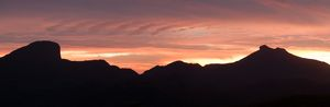 Mountains in the Warrumbungle Range in silhouette at sunset.