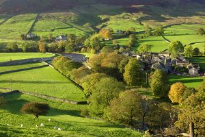 The River Wharfe flowing through fields and past the village of Burnsall.