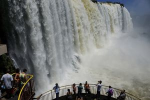 Tourists on viewing platform looking at Iguazu Falls,