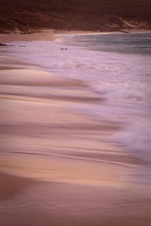 Waves breaking on beach at sunset.