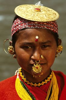 Woman wearing traditional gold-disc hat.