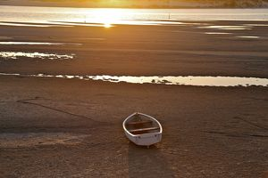 Wooden rowboat stranded on the shore at low tide